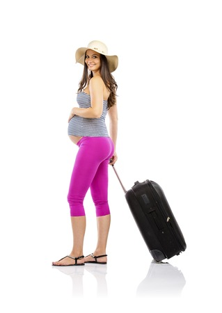 Beautiful pregnant woman in summer clothes and straw hat ready to travel, isolated on white photo