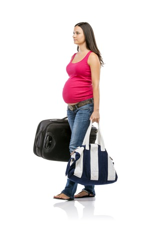 Beautiful pregnant woman with luggage ready to travel, isolated on white Stock Photo