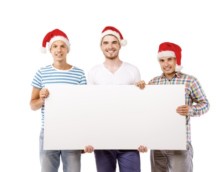 billboard advertising: Three young men in santa hats with copy space, isolated on white background Stock Photo