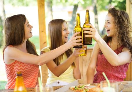 socializando: Tres amigos felices bebiendo cerveza, charlando y divirtiéndose en el jardín de pub Foto de archivo