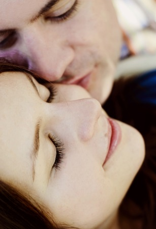 Close up of young couple lying on grass and kissing Stockfoto