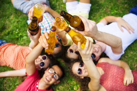 Group of young people having fun in park, lying on the grass with drinks photo