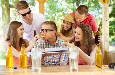 non alcoholic beer: Group of happy friends drinking and eating pizza in pub garden Stock Photo