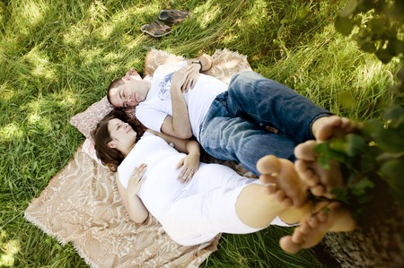 Happy young pregnant couple relaxing and lying on grass photo