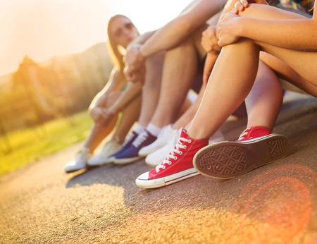 Legs and sneakers of teenage boys and girls sitting on the sidewalk photo