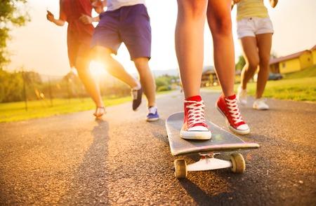 脚とスケート ボード上の若い人たちのスニーカーのクローズ アップ