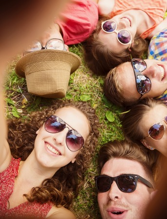 6 people: Group of young people having fun in park, lying on the grass Stock Photo
