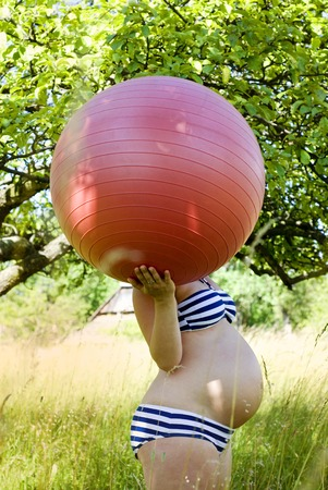 swimming costume: Outdoor portrait of unrecognizable pregnant woman in swimming costume holding fitness ball