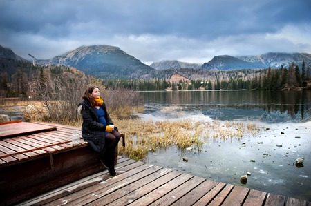 Pregnant woman in autumn clothes sitting on pier and drinking hot drink photo