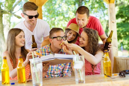 mate drink: Group of happy friends drinking and eating pizza in pub garden Stock Photo