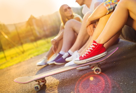 young people group: Closeup of legs and sneakers of young people on skateboard