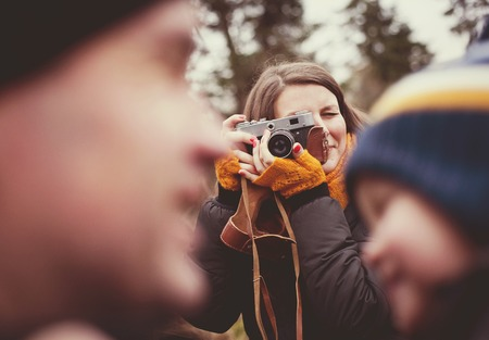 Woman with vintage camera is taking picture of her little son and husband outdoor photo