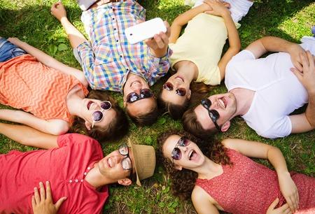 grupo de personas: Grupo de j�venes que se divierten en el parque, tumbado en la hierba y tomando selfie