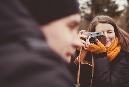 Woman with vintage camera is taking picture of her husband outdoor photo