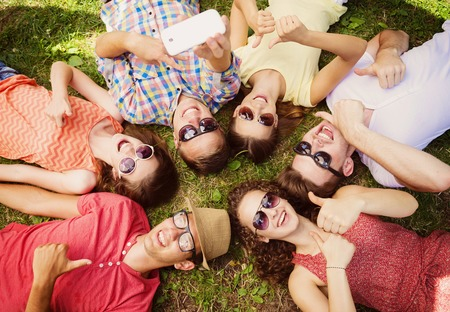 people having fun: Group of young people having fun in park, lying on the grass and taking selfie