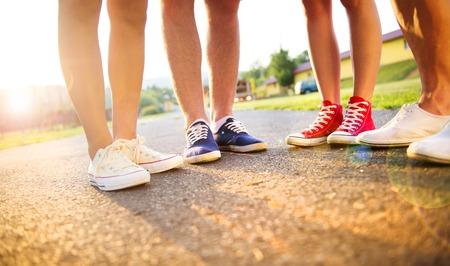 Beine und Turnschuhe von Teenager-Jungen und Mädchen, die auf dem Bürgersteig Standard-Bild - 31533519
