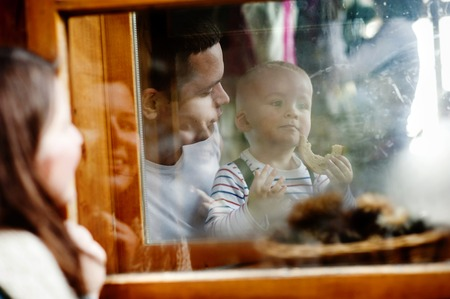 through the window: Happy family is enjoying time together. mother is outside looking through the window to her husband and liitle son Stock Photo