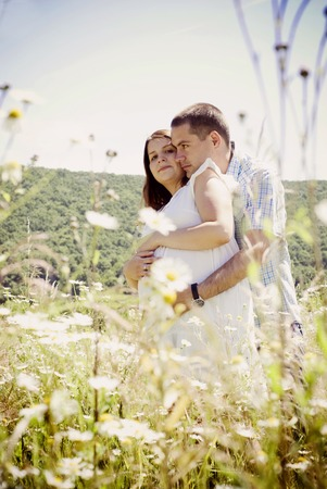 Happy young pregnant couple hugging in nature photo