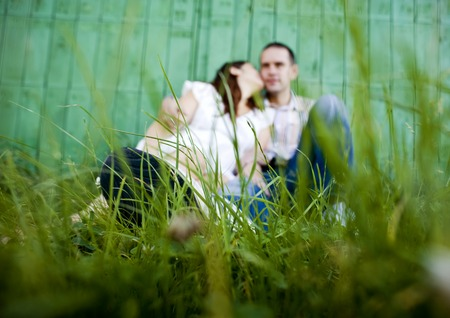 Happy young pregnant couple is relaxing and hugging in front of green fence in nature photo