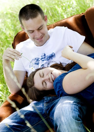 kissing pregnant belly: Happy young pregnant couple relaxing on sofa in nature Stock Photo