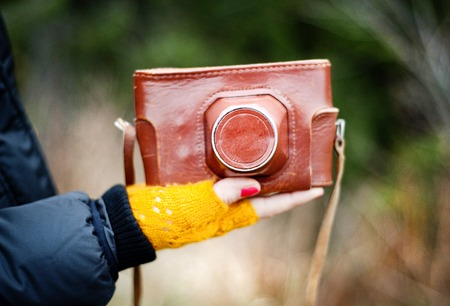 close-up of woman hand holding retro camera in brown leather case photo
