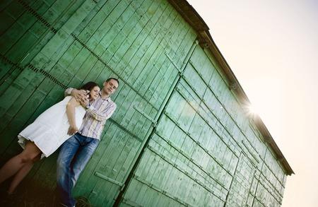 homme enceinte: Heureux jeune couple enceinte est relaxante et étreindre devant clôture verte dans la nature Banque d'images
