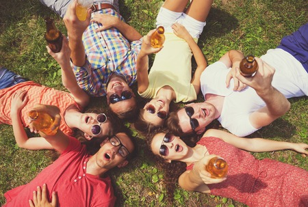 summer drink: Group of young people having fun in park, lying on the grass with drinks