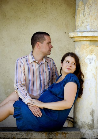 kissing pregnant belly: Happy pregnant couple is relaxing by the old house Stock Photo