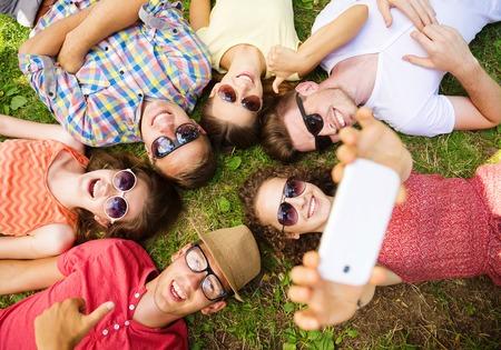 diversion: Grupo de jóvenes que se divierten en el parque, tumbado en la hierba y tomando selfie