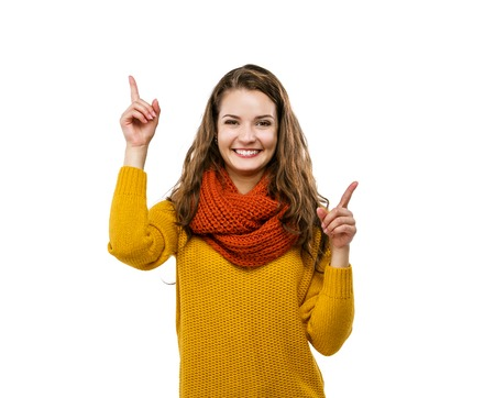 yellow fleece: Portrait of beautiful girl in autumn clothes pointing upwards, isolated on white background