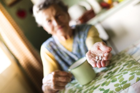 Old woman is taking pills in her country style kitchen photo