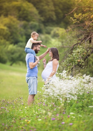 the walk: Happy pregnant family having fun in summer nature
