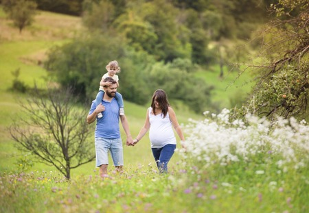 Happy pregnant family having fun in summer nature photo