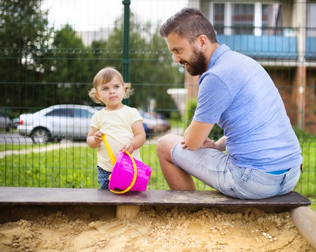 Smiling father and his little daughter playing on playground. photo
