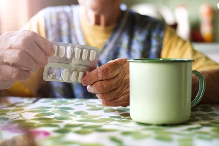 pills in hand: Close up of old womans hands holding pills in kitchen kitchen Stock Photo