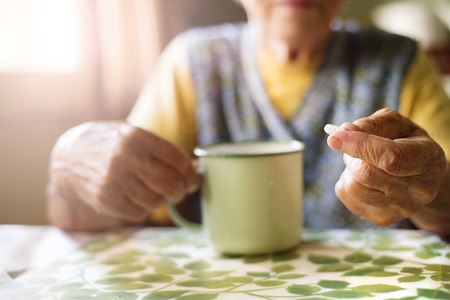 pills hand: Old woman is taking pills in her country style kitchen