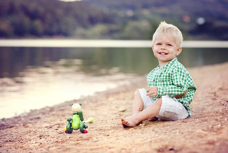 Cute little boy playing with the sand by the lake photo