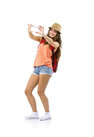 young  brunette: Female tourist taking selfie with cell phone isolated on white background