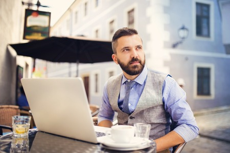 laptop outside: Modern hipster businessman drinking espresso coffee in the city cafe during lunch time and working on laptop