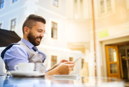 freelancer: Modern hipster businessman drinking espresso coffee in the city cafe during lunch time and using mobile phone
