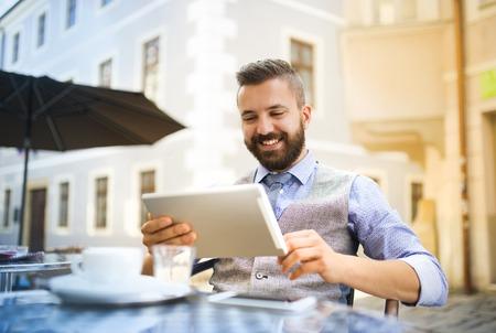 Moderne hipster zakenman het drinken espresso koffie in de stad cafe tijdens de lunch en het werken op tablet Stockfoto