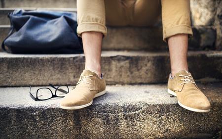 ropa casual: Detalle del inconformista moderno mans pies sentado en las escaleras