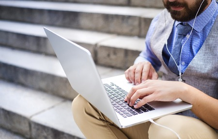 Detail of modern hipster businessman sitting on the stairs and using laptop photo