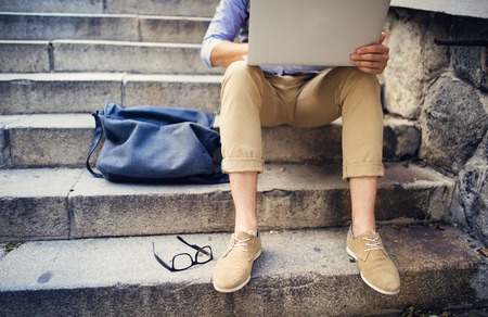 boy feet: Detail of modern hipster man�s feet sitting on the stairs and using laptop
