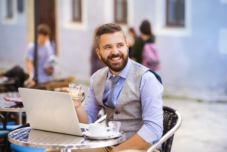 Modern hipster businessman drinking espresso coffee in the city cafe during lunch time and working on laptop