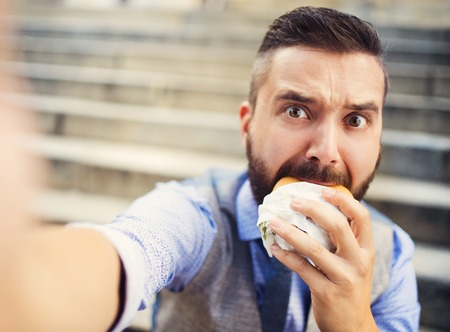 fast eat: Modern hipster businessman having lunch break, sitting on stairs in town center and eating burger