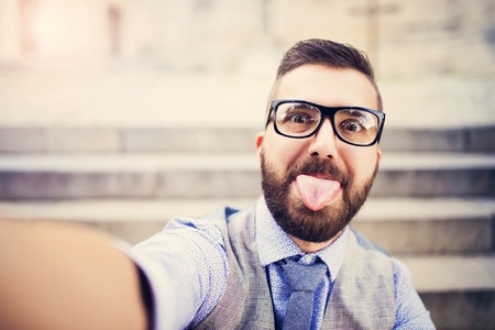 Young hipster businessman taking selfie in city street Stock Photo