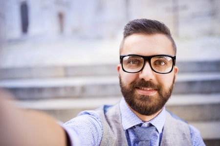 Young hipster businessman taking selfie in city street photo