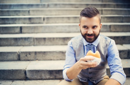 Modern hipster businessman having lunch break, sitting on stairs in town center and eating burger