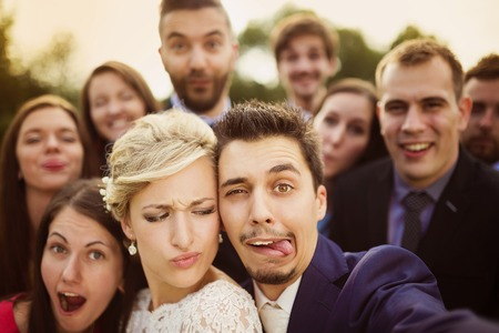 grimacing: Young couple of newlyweds with group of their firends taking selfie and making funny grimaces